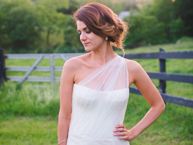 peinado recogido en escote asimétrico en vestido de novia en el campo