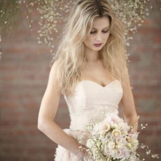 novia con pelo suelto y ramo de flores en mano