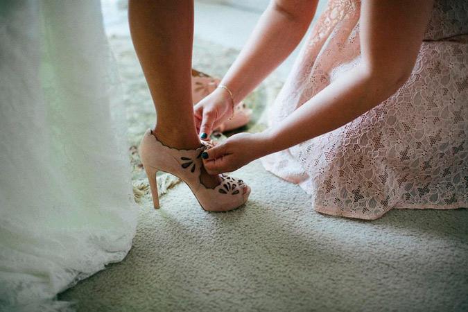 dama de honor anudando los zapatos de la novia
