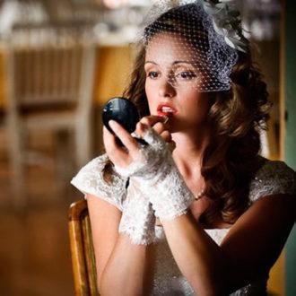 novia pintándose los labios rojos con un espejo de mano