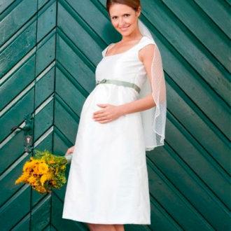 novia embarazada con vestido corto y ramo en la mano
