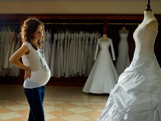 novia embarazada mirando un vestido de novia