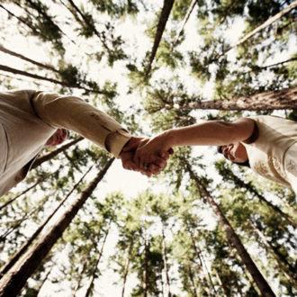 pareja cogiéndose de la mano en su boda en un bosque