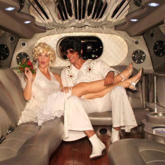 pareja de novios vestidos de Marilyn y Elvis en una limusina