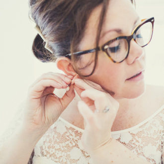 novia con pelo recogido y gafas abrochándose un pendiente
