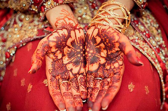 novia con las manos decoradas con henna