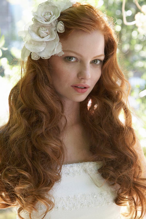 novia con pelo suelto rizado y broche en forma de flor