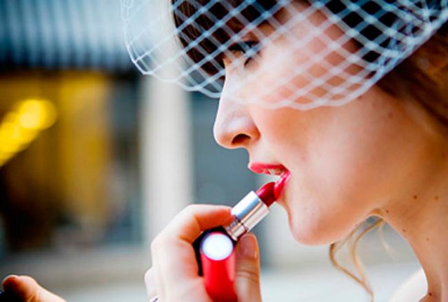 novia con velo birdcage pintándose los labios rojos