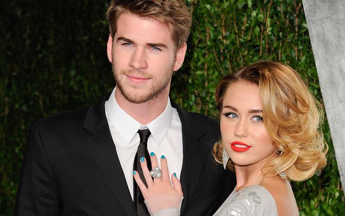 Miley Cyrus y Liam Hemsworth posando para los medios