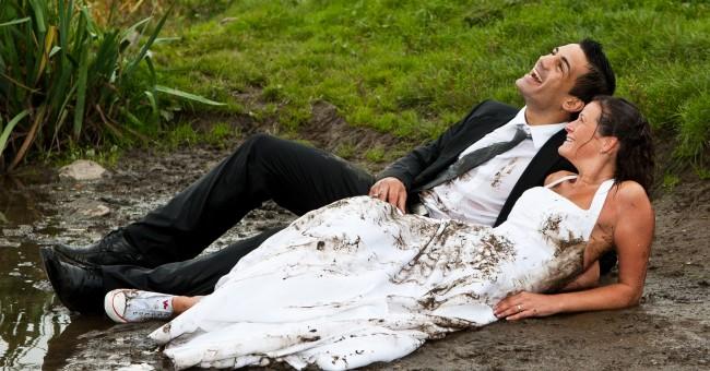pareja de novios en el barro y vestido de novia manchado