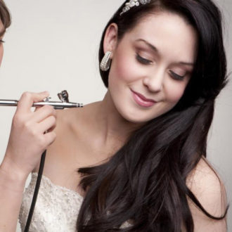 novia aplicándose maquillaje con aerógrafo