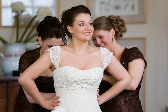 novia con damas de honor ayudándola a cerrar su vestido de boda por la espalda
