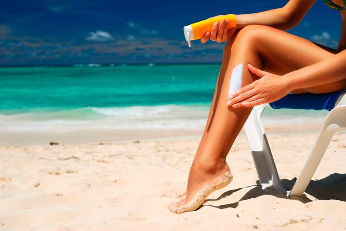 chica poniéndose protector solar en las piernas