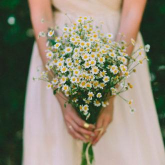 novia sosteniendo ramo de margaritas
