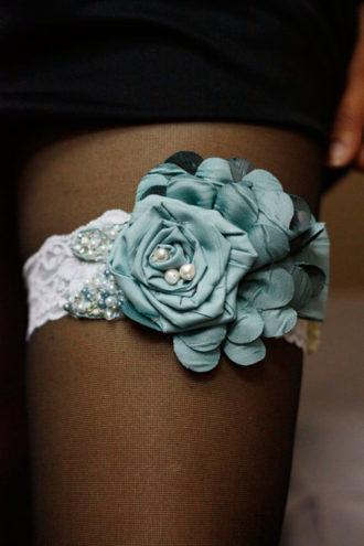 liga blanca con flor azul en pierna de novia