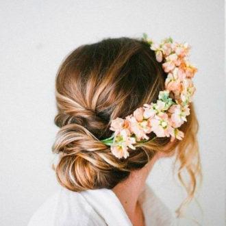 novia con moño bajo e incrustaciones florales
