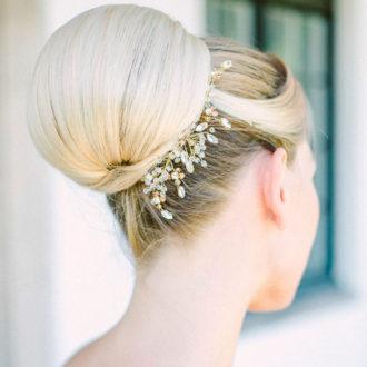 novia con moño medio e incrustaciones florales