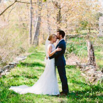 pareja de novios besándose, novia con vestido con cola larga