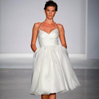 novia con vestido corto con bolsillos en pasarela