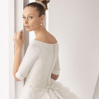 plano medio de novia con vestido de novia de manga larga de Rosa Clará con el pelo recogido