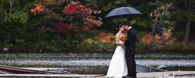 pareja de novios bajo un paraguas en un lago