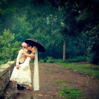 pareja de novios en escena romántica con paraguas bajo la lluvia