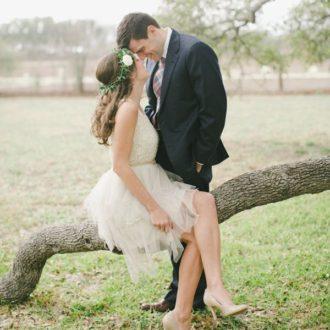 pareja de novios apoyados en árbol y sonriendo en su boda