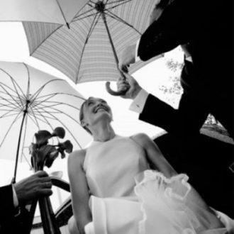 novia bajo los paraguas de invitados de boda blanco y negro