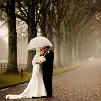 pareja de novios bajo la lluvia en el parque