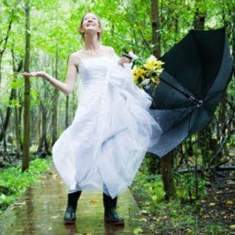 novia con paraguas y botas de agua bajo la lluvia en el bosque