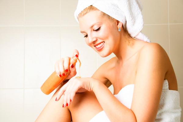 novia recién salida de la ducha aplicándose autobronceador