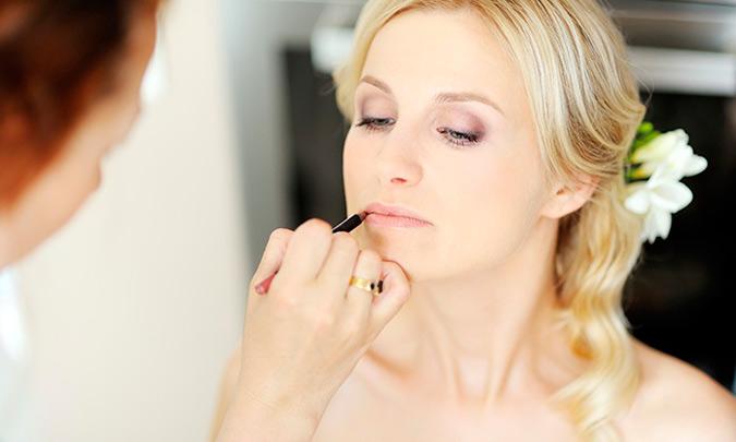 maquilladora perfilando labios de la novia