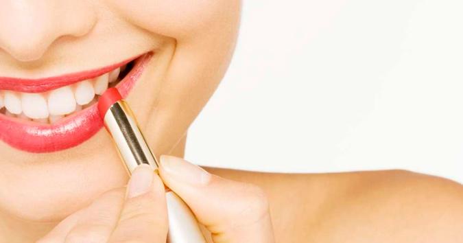 novia sonriendo pintándose los labios de color rojo