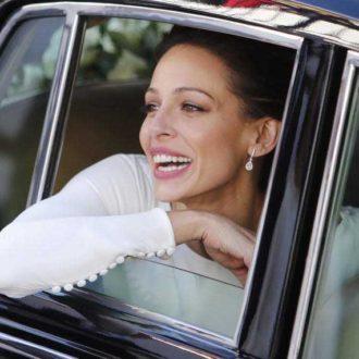 Eva González llegando a su boda sonriendo por la ventanilla del coche