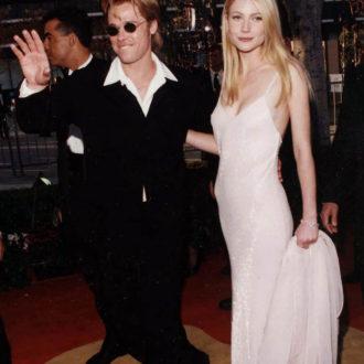 Gwyneth Paltrow con slip dress acompañada por Brad Pitt