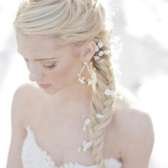 novia rubia con trenza y flores incrustadas