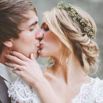 pareja de novios besándose, novia con pelo recogido y corona de flores