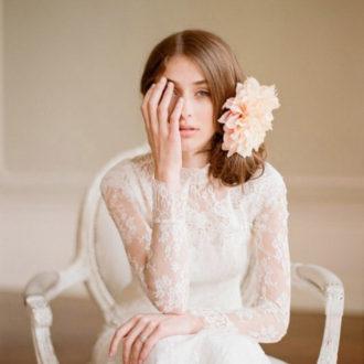 novia sentada con pelo recogido y flores en el lateral