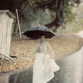 novia al aire libre bajo la lluvia con paraguas y jersey en tono marrón cruzado