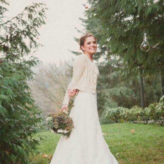 novia al aire libre con chaqueta calada en color blanco y ramo de flores