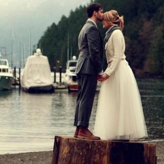 pareja subida en tronco árbol besándose, novia con jersey grueso y bufanda