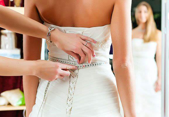 modista tomando medidas en vestido de novia