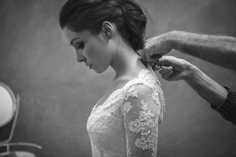 modista cerrando por la espalda el vestido de novia