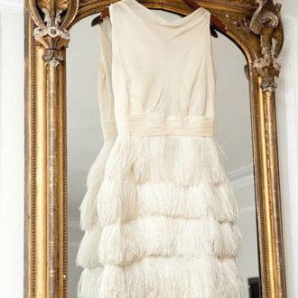 vestido de novia corto con flecos en la falda colgado de percha