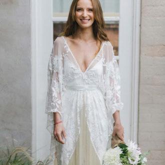 novia con vestido con escote en v, flecos en forma de v y ramo en la mano