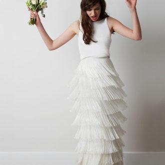 novia con vestido de flecos en la falda y ramo en la mano