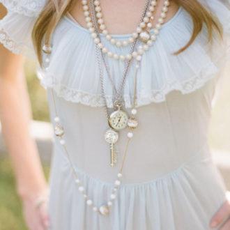 novia con varios collares largos superpuestos con perlas y relojes
