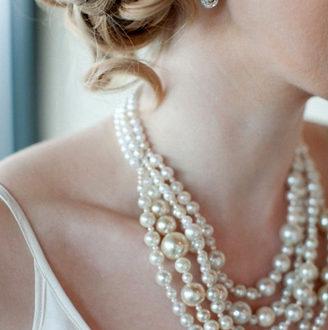 novia con pelo recogido y maxi collar de perlas