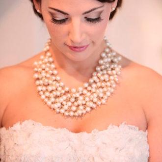 novia con pelo recogido y collar de varias filas de perlas