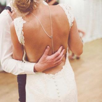 pareja de novios bailando, vestido de novia con espalda descubierta y collar fino en la espalda